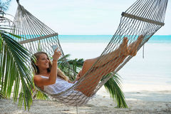 Young beautiful woman lying in a hammock with laptop. Young beautiful woman lying in a hammock with laptop in a tropical Stock Photography