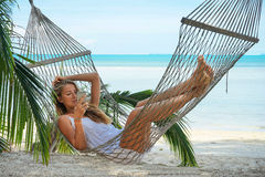 Young beautiful woman lying in a hammock with phone. Young beautiful woman lying in a hammock with phone in a tropical Royalty Free Stock Photo