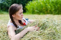 Young beautiful woman lying on hay one summer day Stock Image