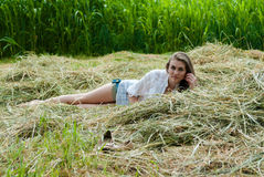 Young beautiful woman lying on hay one summer day Stock Photos