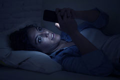 Young beautiful woman lying on home couch using mobile phone internet addiction concept Stock Photo