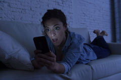 Young beautiful woman lying on home couch using mobile phone internet addiction concept Stock Image