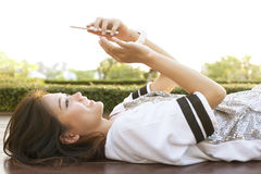 Young beautiful woman lying on home terrace and playing smart ph Stock Images