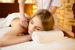 Young beautiful woman lying on a massage table and is being massaged Royalty Free Stock Photography