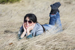 Young beautiful woman lying in a meadow with dry grass Stock Image