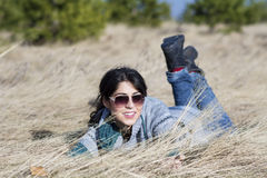 Young beautiful woman lying in a meadow with dry grass Stock Photo