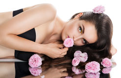 Young beautiful woman is lying near the mirror with its reflection. Royalty Free Stock Photos