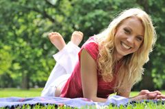 Young beautiful woman lying outdoors Stock Photography