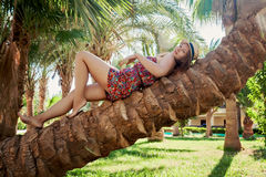 Young beautiful woman lying on a palm tree Royalty Free Stock Photo