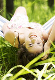 Young beautiful woman lying and relaxing in a hammock. Royalty Free Stock Photos