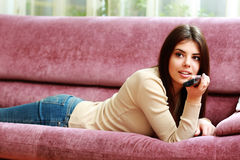 Young beautiful woman lying on the sofa with remote control Royalty Free Stock Image