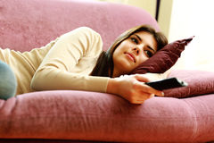 Young beautiful woman lying on the sofa with remote control Royalty Free Stock Images