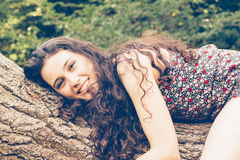 Young beautiful woman lying on a trunk Stock Image