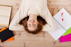 Young beautiful woman lying on the wooden with books. Stock Photography