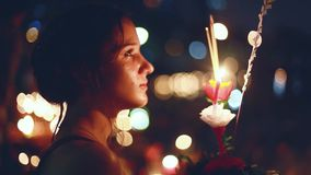 Young beautiful woman makes a wish in a carnival to celebrate the Loy Krathong Festival. 1920x1080. Young beautiful woman in a carnival to celebrate the Loy stock video footage