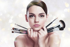 Young beautiful woman with makeup brushes near her face, skin care concept Stock Photos