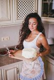 Young beautiful woman making cake at the kitchen Stock Images