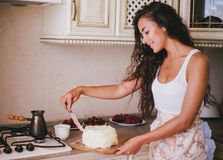 Young beautiful woman making cake at the kitchen. Young beautiful woman making cake with fresh berries and white icing at the kitchen Royalty Free Stock Photo