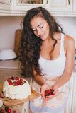 Young beautiful woman making cake at the kitchen. Young beautiful woman making cake with fresh berries and white icing at the kitchen Royalty Free Stock Photos