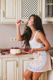 Young beautiful woman making cake at the kitchen. Young beautiful woman making cake with fresh berries and white icing at the kitchen Royalty Free Stock Images