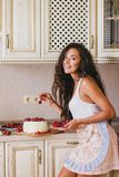 Young beautiful woman making cake at the kitchen. Young beautiful woman making cake with fresh berries and white icing at the kitchen Stock Photography