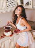 Young beautiful woman making cake at the kitchen. Young beautiful woman making cake with fresh berries and white icing at the kitchen Stock Photos