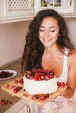 Young beautiful woman making cake at the kitchen. Young beautiful woman making cake with fresh berries and white icing at the kitchen Royalty Free Stock Photography