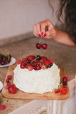 Young beautiful woman making cake at the kitchen. Young beautiful woman making cake with fresh berries and white icing at the kitchen Stock Images