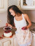 Young beautiful woman making cake at the kitchen. Young beautiful woman making cake with fresh berries and white icing at the kitchen Royalty Free Stock Image