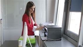 Young beautiful woman making copies of files in the copy machine. stock video footage
