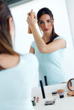 Young beautiful woman making hairstyle near mirror. Royalty Free Stock Photography