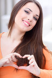Young beautiful woman making a heart sign Stock Images