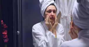 Young beautiful woman making herself face massage in the bathroom stock video
