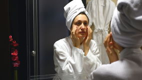 Young beautiful woman making herself face massage in the bathroom stock video footage