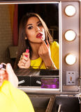 Young beautiful woman making make-up near mirror Stock Image