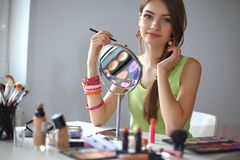 Young beautiful woman making make-up near mirror Royalty Free Stock Images