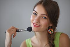 Young beautiful woman making make-up near mirror Stock Photos