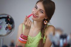 Young beautiful woman making make-up near mirror Stock Photo