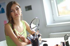 Young beautiful woman making make-up near mirror Royalty Free Stock Photo