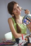 Young beautiful woman making make-up near mirror Stock Image