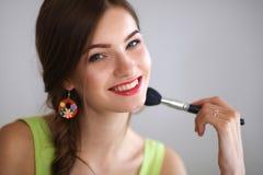 Young beautiful woman making make-up ,sitting at Stock Photography