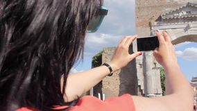 Young beautiful woman making mobile photo of ancient city stock video