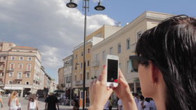 Young beautiful woman making mobile photo of ancient city stock footage