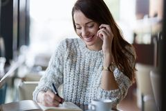 Young beautiful woman making phone call in cafe. Young happy beautiful woman making phone call in cafe Stock Photography