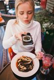 Young beautiful woman making photo of black pasta with seafood and cuttlefish ink royalty free stock image