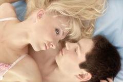 Young beautiful woman and a man lying down on bed looking at each other Royalty Free Stock Photos