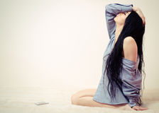 Young beautiful woman in man's shirt sitting on sofa alone stock photography
