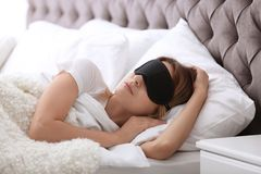Young beautiful woman with mask sleeping. In bed at home. Early morning stock image