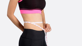 Young beautiful woman measuring her waist. Royalty Free Stock Photos