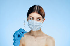 Young beautiful woman in a medical mask on a blue background holds a syringe, plastic surgery.  Royalty Free Stock Images